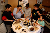 Inuit family eating traditional foods at a Birthday party in Qaanaaq. N.W.Greenland. 1998