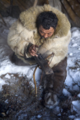 Grisha Rahtyn, a Chukchi reindeer herder, prepares to make fire with a bow drill & traditional fire making device during a ritual. Chukotskiy Peninsula, Chukotka, Siberia, Russia