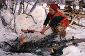 Olga Gilova, an Evenk woman cooking reindeer meat over an open fire. Evenkiya, Siberia, Russia. 1997