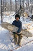 Victor Ivanovich, an Evenk reindeer herder, at his winter camp in the forest holds a pair of traditional Evenk reindeer skin covered skis. Surinda, Evenkiya, Central Siberia, Russia. 1997