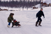 An Evenk boy and girl pulling a baby on a toboggan in Surinda. Evenkiya, Siberia, Russia. 1997