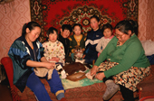 An Evenk family at their home in Surinda. Sewing and with puppy. Evenkiya, Central Siberia, Russia. 1997