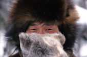 In the cold of winter, Andrei Dulubchin, an Evenk man warms his nose with his reindeer skin mitten. Evenkiya, Siberia, Russia. 1997