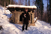 A Russian hunter outside his wooden hut in the forest near Tura. Evenkiya, Central Siberia, Russia. 1997