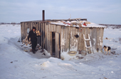 Vassily Selivanov, a Sami reindeer herder from Lovozero, carries firewood into his hut. Murmansk, NW Russia. 2005