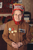 Maria Zakharova, an 82 year old Sami woman, wearing a jacket with her Soviet medals in her apartment in Lovozero. Murmansk, Kola Peninsula, NW Russia. 2005