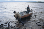 Sami men return to their summer camp in a wooden boat after checking their fishing nets near Lovozero. Kola Peninsula, NW Russia. 2005