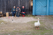 Children seated outside a house in Pogost village watch a goose wander by. Ryazan Province, Russia. 2006
