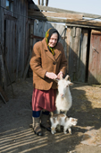 Maria, an elderly woman,  at her home in Pogost Village with her goat Rosa, and her cat. Ryazan Province, Russia. 2006