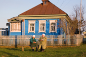 Two elderly women chat while sitting on a bench outside a wooden house in the village of Giblitsy. Ryazan Province, Russia. 2006