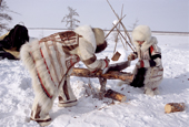 Nganasan women in traditional dress sawing firewood at a camp on the bank of the Kheta River. Taymyr, Northern Siberia, Russia. 2004