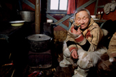 Saibore Momde, a Nganasan elder, smokes his pipe while relaxing in a hut at a camp on the Kheta River. Taymyr, Northern Siberia, Russia. 2004
