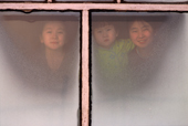 Lena Potapova & her sisters Varya & Tanya look through a window at their home in Verkhoyansk, Yakutia Siberia