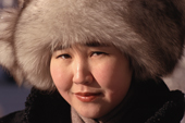 A young Yakut woman dressed for winter's cold in a fox fur hat coat. Yakutsk, Yakutia, Siberia, Russia.