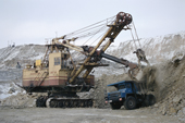 A giant digger loads ore into the back of truck at an open mine near Norilsk. Western Siberia, Russia.