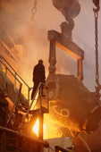 A worker is silhouetted by red hot metal at the copper foundry in Norilsk. Western Siberia, Russia.