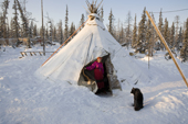 Pavla Nogo, a Komi woman, in the entrance of her reindeer skin tent at a winter camp. Yamal, Northwest Siberia, Russia