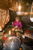 With the light from oil lamps, Pavla Nogo, a Komi woman, sews a reindeer skin boot in her tent. Yamal, Northwest Siberia, Russia
