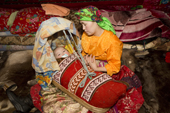 Marina Valeeva, a young Komi woman,rocks her baby daughter, Albina, to sleep in a traditional cradle at their winter camp. Yamal, Western Siberia, Russia
