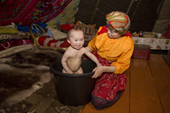 Marina Valeeva, a Komi woman, bathes her young daughter Albina in a plastic bucket inside their tent at a winter camp. Yamal, Westren Siberia, Russia
