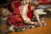 Marina Valeeva, a Komi woman, prepares to cut a pattern from a reindeer skin on the floor of her tent, which she will use to make a coat for her daughter. Yamal, Western Siberia, Russia