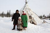 A Komi couple, Nikolai Valeev and his wife Marina together with their daughter Anastasia, outside their reindeer skin tent at a winter camp. Yamal, Western Siberia, Russia