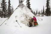 Marina Valeeva, a Komi woman, stands at the entrance to her family's tent at their winter camp in the forest. Priuralsky District, Yamal, NW Siberia.