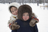 Albina Valeeva, a young Komi girl (left),playing outside with her brother, Matvey, at their family's winter camp in the forest. Priuralsky District, Yamal, NW Siberia.