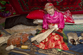 Marina Valeeva, a Komi woman, repairing a reindeer skin boot inside her familys' tent at at a winter camp in the forest. Priuralsky District, Yamal, NW Siberia.