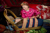 Marina Valeeva, a Komi woman,settles her 6 month old baby, Tonya, in her cradle, at a winter camp in the forest. Priuralsky District, Yamal, NW Siberia.
