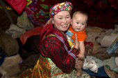 Marina Valeeva, a young Komi woman, holds her six month old baby daughter, Tonya, inside her family's tent at a winter camp in the forest. Priuralsky District, Yamal, NW Siberia.