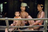 Mentawai men catch the breeze at the entrance of an Uma. Siberut Is. Indonesia.