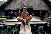 Mentawai boy in front of  small house made of Sago Palm leaves and local woods. Matotonan, Siberut, Indonesia.