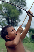 Mentawai boy plays with bow & arrow & shooting monkeys. Matotonan. Siberut.Indonesia