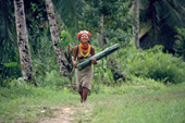 Mentawai woman returns with leaves she uses to cook sago in. Siberut Is. Indonesia.