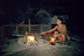 A Mentawai man bakes sago in bamboo sticks over a fire. Siberut. Indonesia