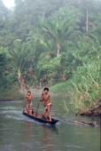 Mentawai men travel in a dugout canoe on the Rereiket river. Siberut, Indonesia.