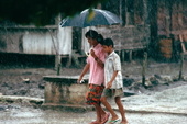 Children walking through the monsoon rains. Sumatra. Indonesia.