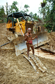 Mentawai medicine man stands on broken bulldozer in his rainforest. Indonesia.