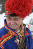 Sami man in a traditional red pompom hat leads the procession at Jokkmokk's Winter Market. Sweden. Size to A4