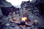 Yak herders sit by the fire and make butter in goats skins. Ladakh, India