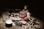 Yak herder's wife nurses her baby in a stone shelter. Ladakh. India.